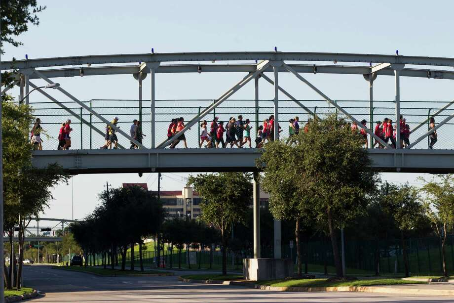 Runners cross the Kirby Dr. bridge as they run the course during the 3rd Annual Running of the Bulls 5K Run/Walk at Reliant Park on Sunday, Sept. 22, 2013, in Houston. Over 5,500 people participated in the event with the proceeds benefiting the Houston Texans Foundation and Houston Methodist. Photo: J. Patric Schneider, For The Chronicle / © 2013 Houston Chronicle