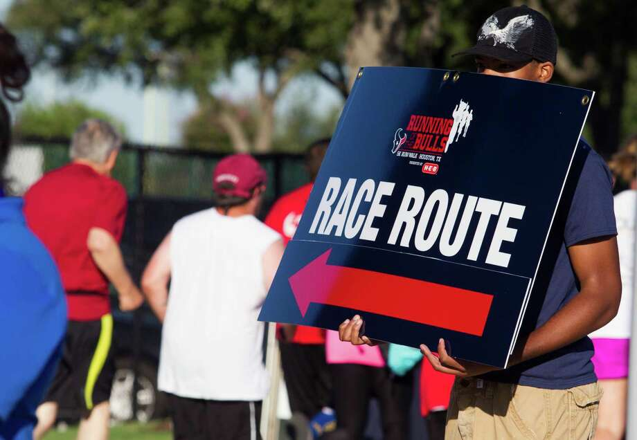 A volunteer points runners in the right direction during the 3rd Annual Running of the Bulls 5K Run/Walk at Reliant Park on Sunday, Sept. 22, 2013, in Houston. Over 5,500 people participated in the event with the proceeds benefiting the Houston Texans Foundation and Houston Methodist. Photo: J. Patric Schneider, For The Chronicle / © 2013 Houston Chronicle