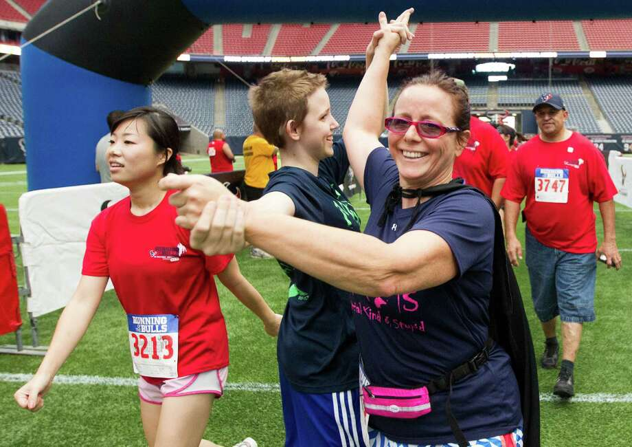Allie Triplett, 13, congratulates her mother Jennifer as they cross the finish line during the 3rd Annual Running of the Bulls 5K Run/Walk at Reliant Park on Sunday, Sept. 22, 2013, in Houston. Over 5,500 people participated in the event with the proceeds benefiting the Houston Texans Foundation and Houston Methodist. Photo: J. Patric Schneider, For The Chronicle / © 2013 Houston Chronicle