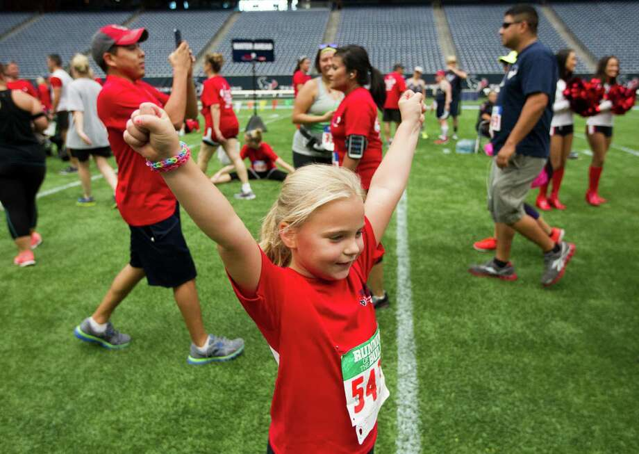 Kali Navarro, 6, celebrates after she crosses the finish line during the 3rd Annual Running of the Bulls 5K Run/Walk at Reliant Park on Sunday, Sept. 22, 2013, in Houston. Over 5,500 people participated in the event with the proceeds benefiting the Houston Texans Foundation and Houston Methodist. Photo: J. Patric Schneider, For The Chronicle / © 2013 Houston Chronicle