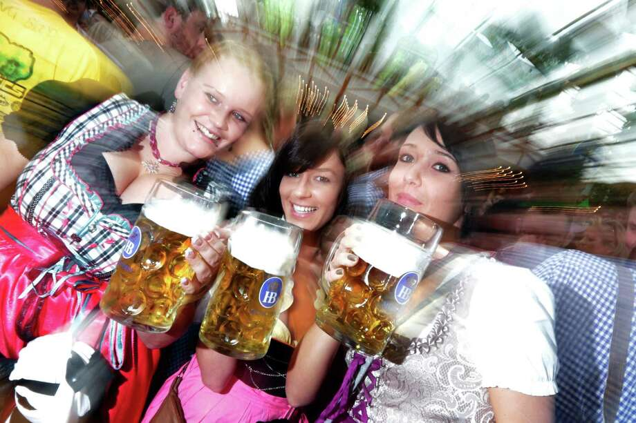 "Young people celebrate the opening ceremony in the ""Hofbraeuzelt' beer tent of the 180th Bavarian ""Oktoberfest"" beer festival in Munich, southern Germany, Saturday, Sept. 21, 2013. The world's largest beer festival, to be held from Sept. 21 to Oct. 6, 2013 will attract more than six million guests from around the world. Photo: AP"