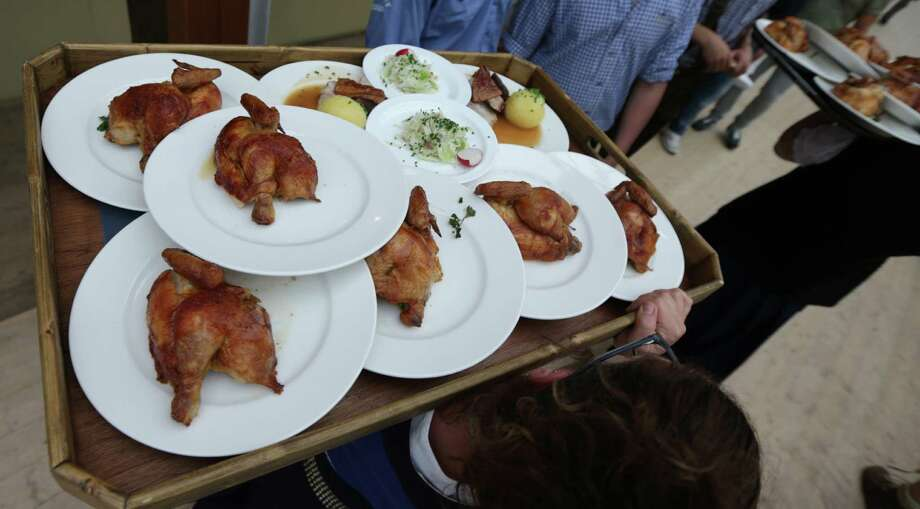 "A waitress carries chicken during the opening ceremony in the ""Hofbraeuzelt' beer tent of the 180th Bavarian ""Oktoberfest"" beer festival in Munich, southern Germany, Saturday, Sept. 21, 2013. The world's largest beer festival, to be held from Sept. 21 to Oct. 6, 2013 will attract more than six million guests from around the world. Photo: AP"