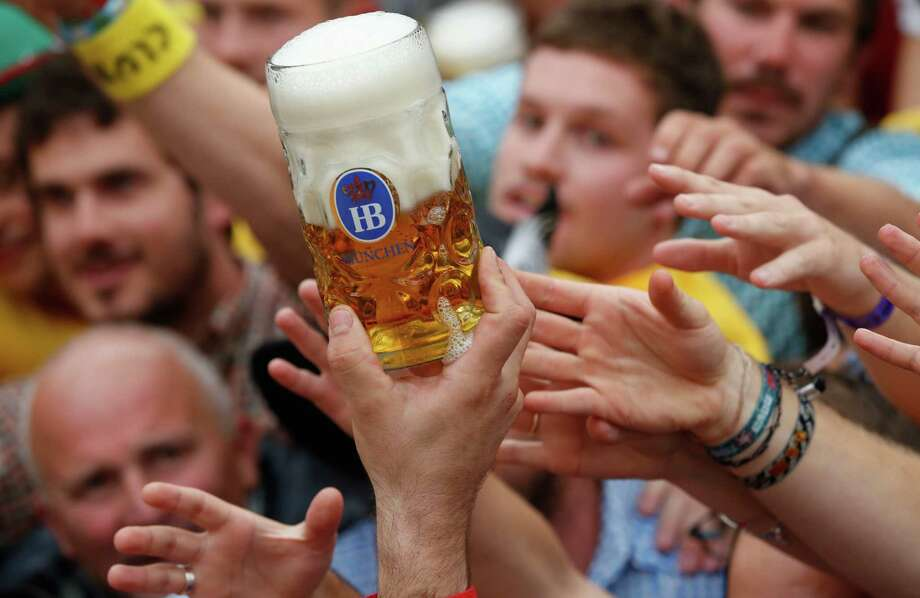 "Young people fight for the first beer during the opening ceremony in the ""Hofbraeuzelt' beer tent of the 180th Bavarian ""Oktoberfest"" beer festival in Munich, southern Germany, Saturday, Sept. 21, 2013. The world's largest beer festival, to be held from Sept. 21 to Oct. 6, 2013 will attract more than six million guests from around the world. Photo: AP"