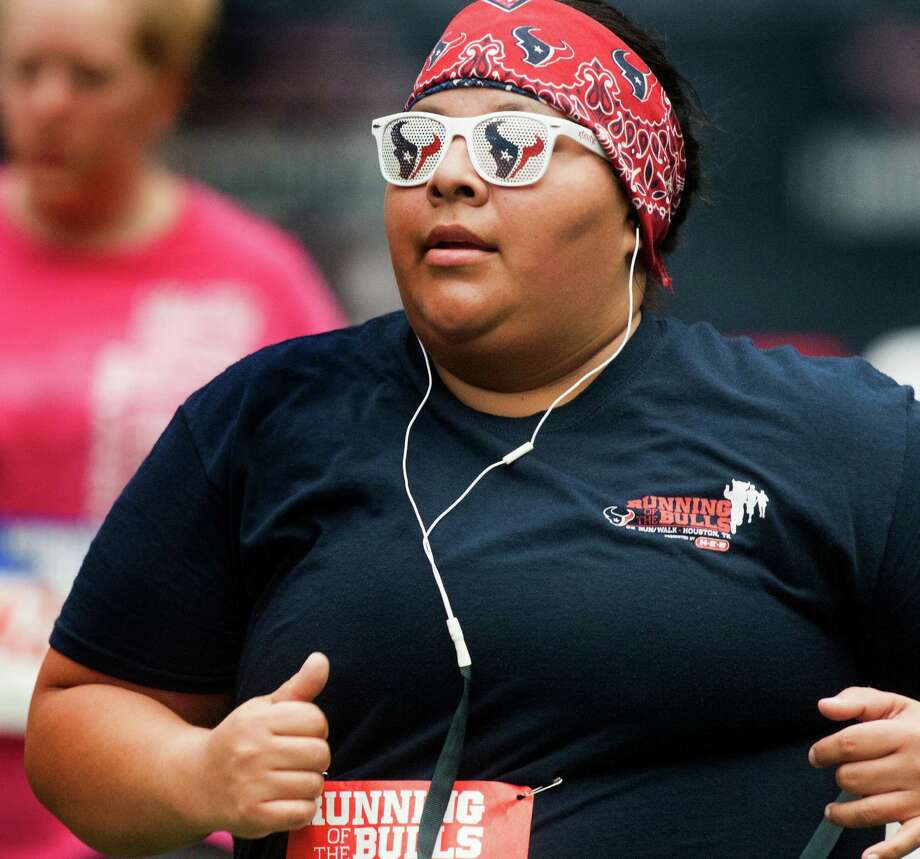 A runner wears her Texans glasses as she runs the course during the 3rd Annual Running of the Bulls 5K Run/Walk at Reliant Park on Sunday, Sept. 22, 2013, in Houston. Over 5,500 people participated in the event with the proceeds benefiting the Houston Texans Foundation and Houston Methodist. Photo: J. Patric Schneider, For The Chronicle / © 2013 Houston Chronicle