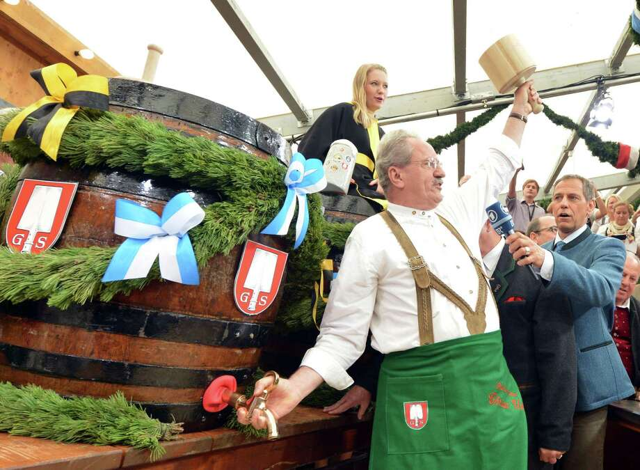 "Munich's mayor Christian Ude tapping  the first  keg of beer   during the opening ceremony  of the 180th Bavarian ""Oktoberfest"" beer festival in Munich, southern Germany, Saturday, Sept. 21, 2013. The world's largest beer festival, to be held from Sept. 21 to Oct. 6, 2013 will attract more than six million guests from around the world. Photo: AP"