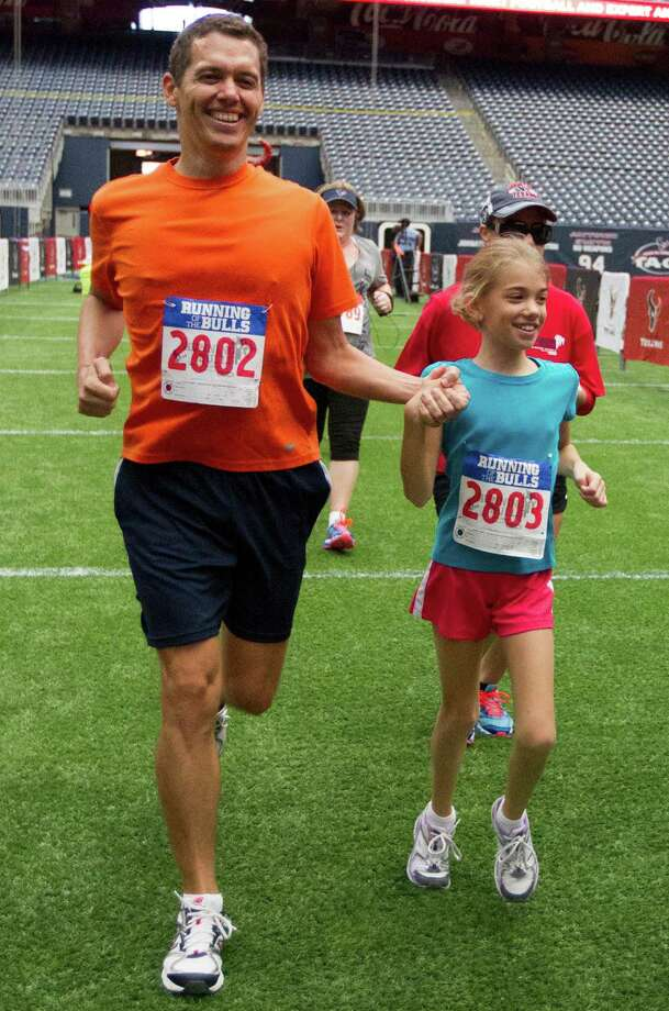 Juan Varinaga holds hands with his daughter Analys, 10, as they cross the finish line during the 3rd Annual Running of the Bulls 5K Run/Walk at Reliant Park on Sunday, Sept. 22, 2013, in Houston. Over 5,500 people participated in the event with the proceeds benefiting the Houston Texans Foundation and Houston Methodist. Photo: J. Patric Schneider, For The Chronicle / © 2013 Houston Chronicle