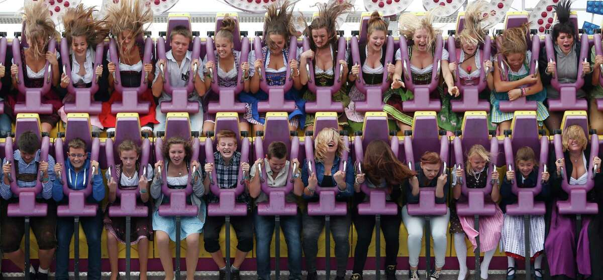 People enjoy a fairground ride at the opening day of the Bavarian
