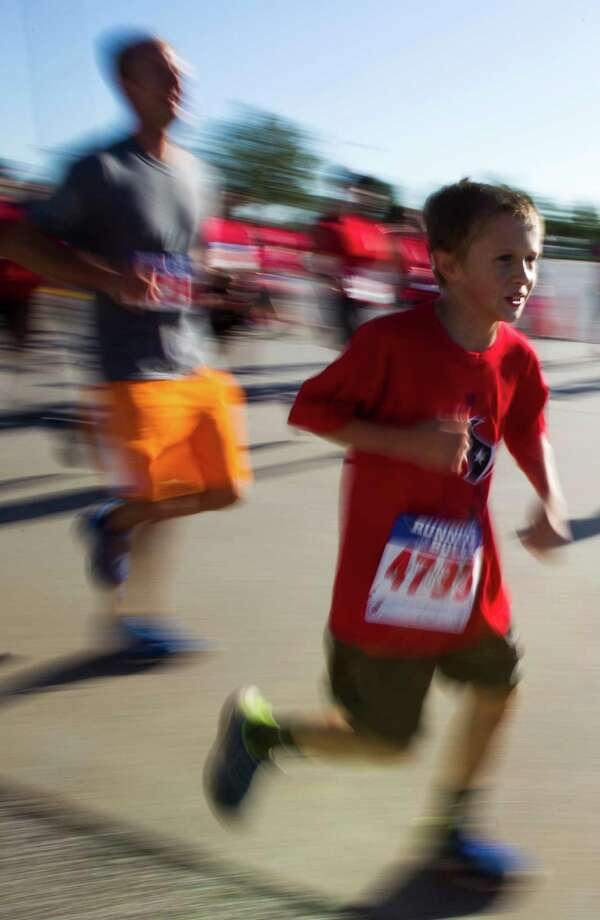 A young runner runs the course during the 3rd Annual Running of the Bulls 5K Run/Walk at Reliant Park on Sunday, Sept. 22, 2013, in Houston. Over 5,500 people participated in the event with the proceeds benefiting the Houston Texans Foundation and Houston Methodist. Photo: J. Patric Schneider, For The Chronicle / © 2013 Houston Chronicle