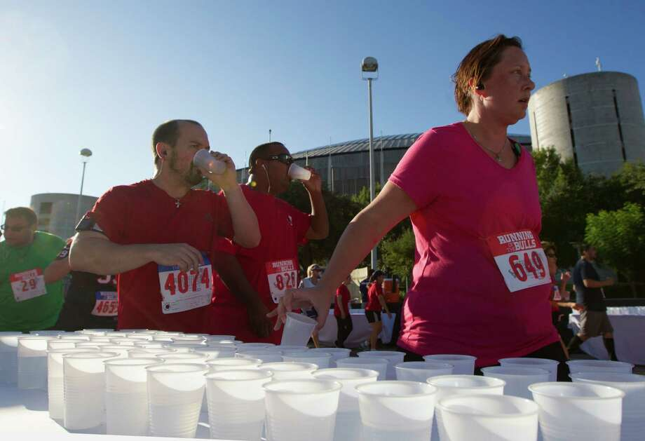 Runners get a water break as they run the course during the 3rd Annual Running of the Bulls 5K Run/Walk at Reliant Park on Sunday, Sept. 22, 2013, in Houston. Over 5,500 people participated in the event with the proceeds benefiting the Houston Texans Foundation and Houston Methodist. Photo: J. Patric Schneider, For The Chronicle / © 2013 Houston Chronicle