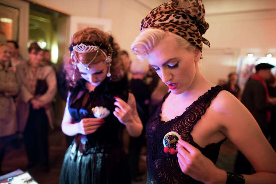 Burlesque artist Minouche von Marabou of Switzerland, left, and Little Miss Piss of Germany try out nipples pasties at a sales booth during the Newcomer Night of the first international Berlin Burlesque Festival in Berlin, Germany, Thursday, Sept. 19, 2013. The four-day festival including three different evening shows and different workshops hosts some 36 international burlesque artists. Photo: AP