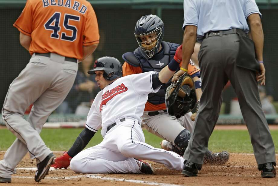 Asdrubal Cabrera, center, slides home under the tag from Astros catcher Carlos Corporan to score on a single by Mike Aviles in the fourth inning. Photo: Mark Duncan, Associated Press