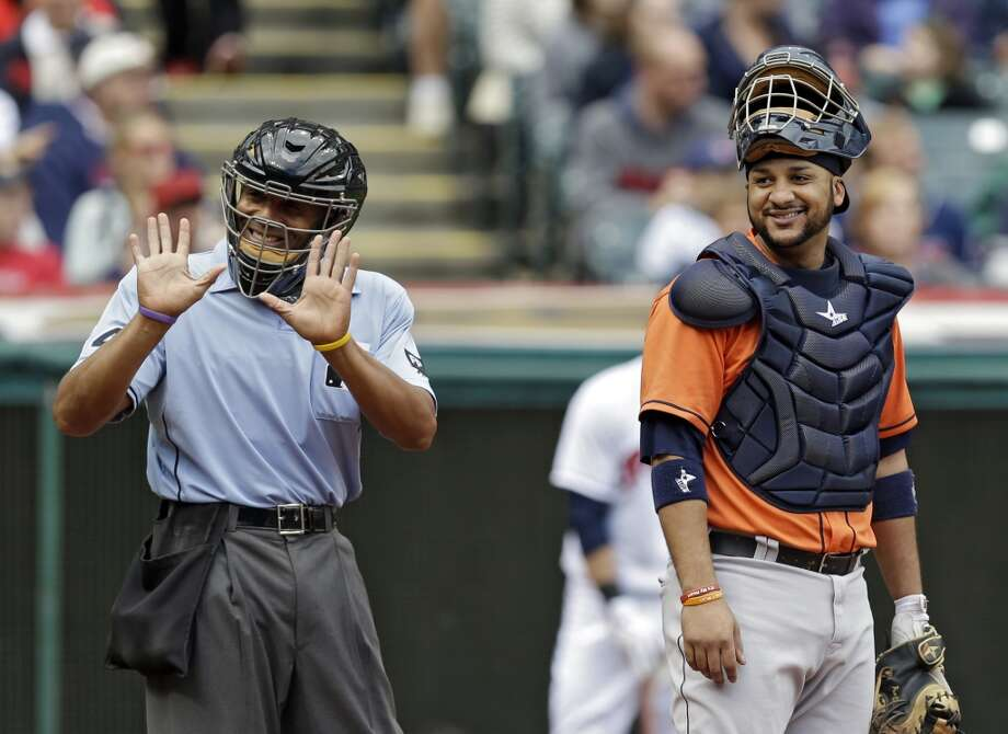 Home plate umpire CB Bucknor gestures toward the Astros dugout as catcher Carlos Corporan laughs in the fourth inning. Photo: Mark Duncan, Associated Press
