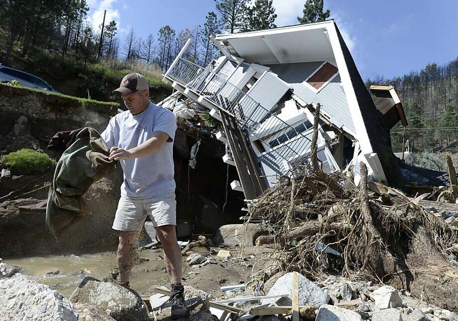 Sean McCroskey pulls possessions out of the debris in the river in front of his destroyed home in Boulder County, Colo. Mountain towns will be cut off until roads are rebuilt. Photo: Jeremy Papasso, Associated Press