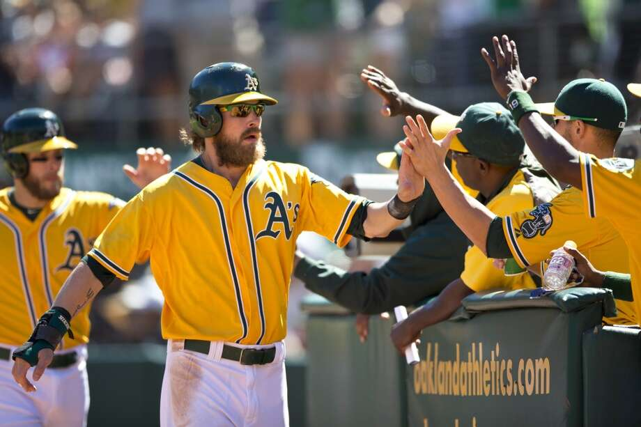 Josh Reddick is congratulated by teammates after scoring a run against the Minnesota Twins during the second inning at O.co Coliseum on September 22, 2013 in Oakland, California. Photo: Jason O. Watson, Getty Images