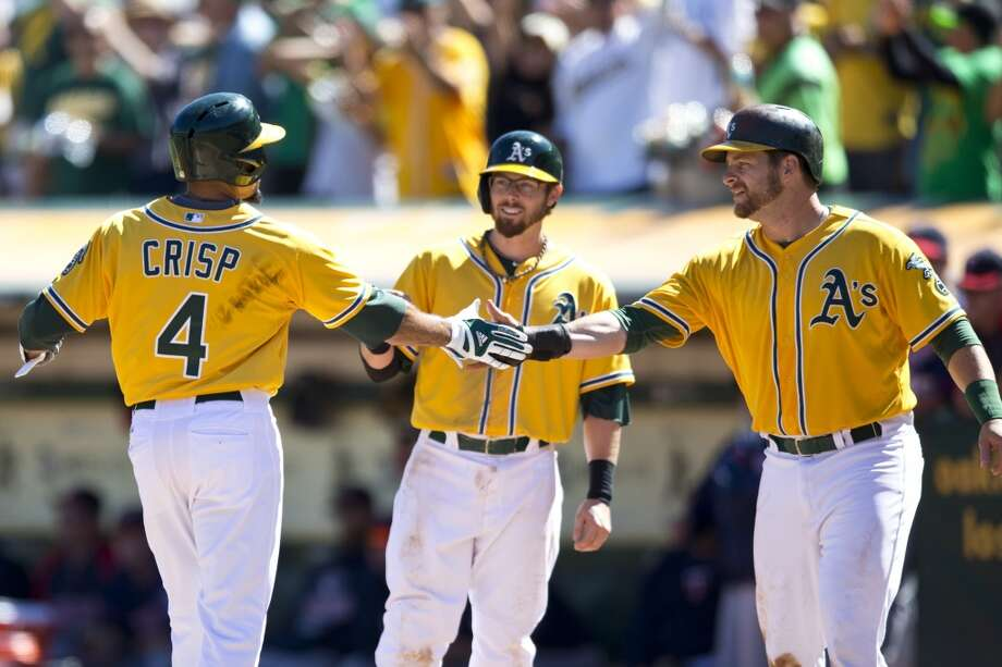 Coco Crisp is congratulated by teammates after hitting a three run home run against the Minnesota Twins during the second inning at O.co Coliseum on September 22, 2013 in Oakland, California. Photo: Jason O. Watson, Getty Images