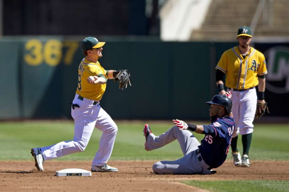 OAKLAND, CA - SEPTEMBER 22: Jed Lowrie #8 of the Oakland Athletics completes a double play over Pedro Florimon #25 of the Minnesota Twins during the second inning at O.co Coliseum on September 22, 2013 in Oakland, California. Photo: Jason O. Watson, Getty Images