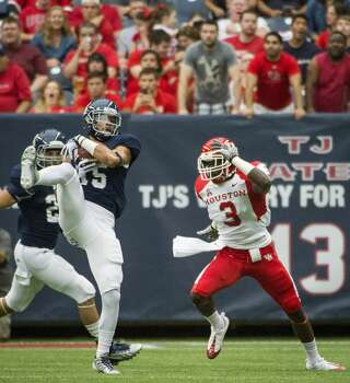 Rice cornerback Phillip Gaines intercepts a pass intended for Houston wide receiver Deontay Greenberry. Photo: Smiley N. Pool, Houston Chronicle