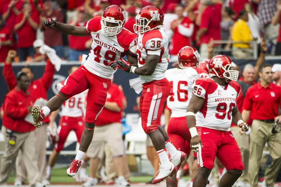Houston linebackers Derrick Mathews (49) and George Bamfo celebrate as time expires on the annual Bayou Bucket game. Photo: Smiley N. Pool, Houston Chronicle
