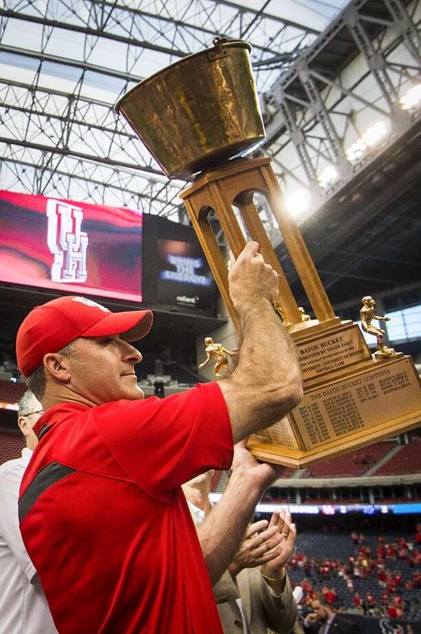 Houston head coach Tony Levine raises the Bayou Bucket. Photo: Smiley N. Pool, Houston Chronicle