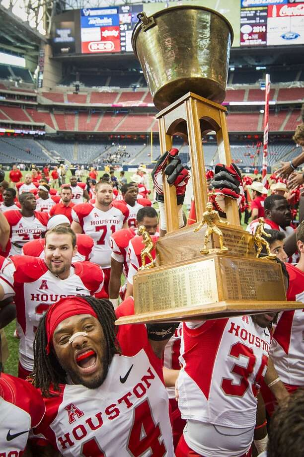 Houston defensive backs Jarrett Irving (14) and  Steven Aikens (39) carry the Bayou Bucket trophy off the field following the victory. Photo: Smiley N. Pool, Houston Chronicle