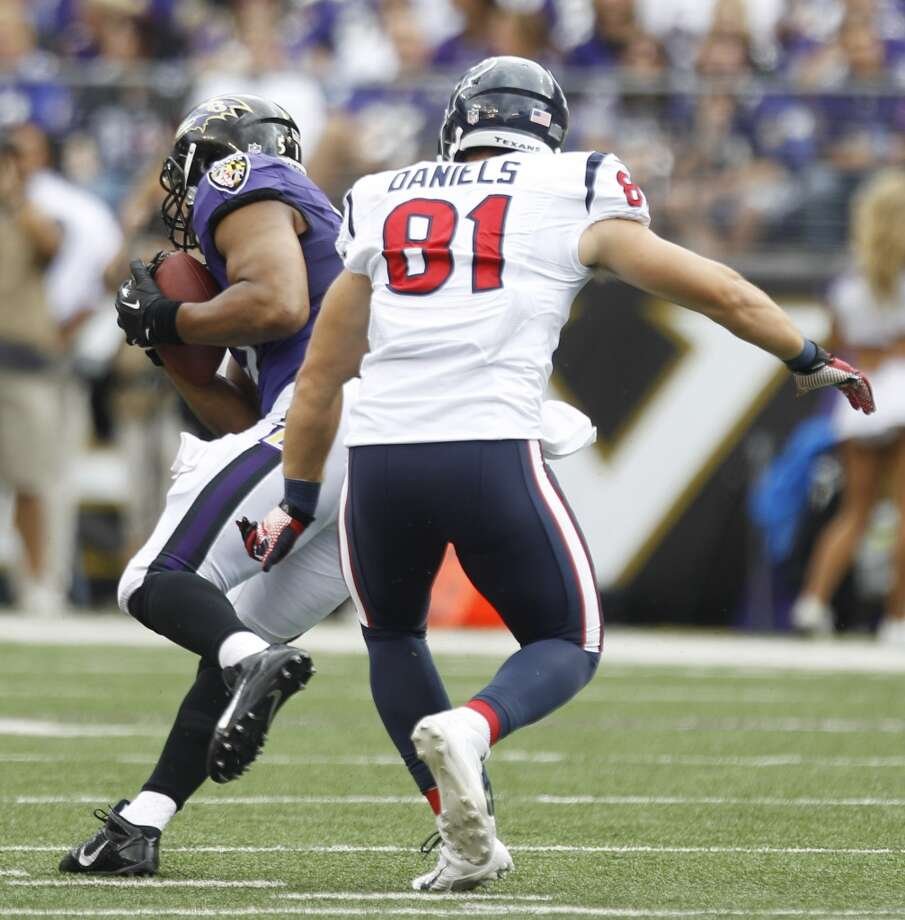 Daryl Smith of the Ravens gets an interception in front of Texans tight end Owen Daniels. Photo: Brett Coomer, Houston Chronicle