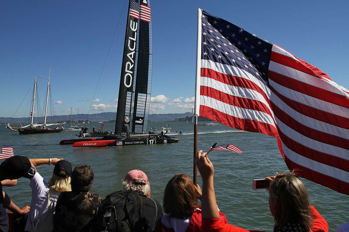Spectators cheer and wave flags as Oracle Team USA passes by the America's Cup Pavilion on Sunday, Sept. 22, 2013. Fans gathered at the America's Cup Pavilion in the Embarcadero to watch Oracle Team USA go head-to-head with Emirates Team New Zealand in Races 14 and 15.