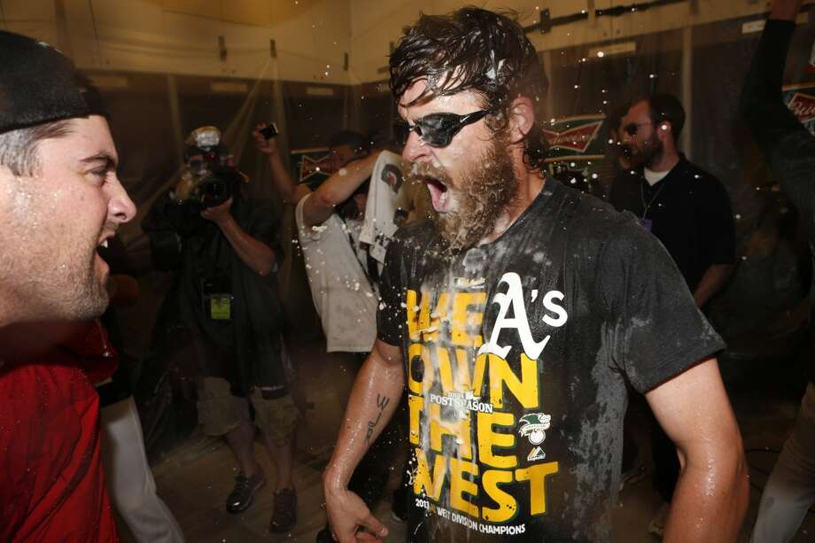 Josh Reddick is doused by teammates in the A's postgame division championship celebration. Photo: Beck Diefenbach, Associated Press