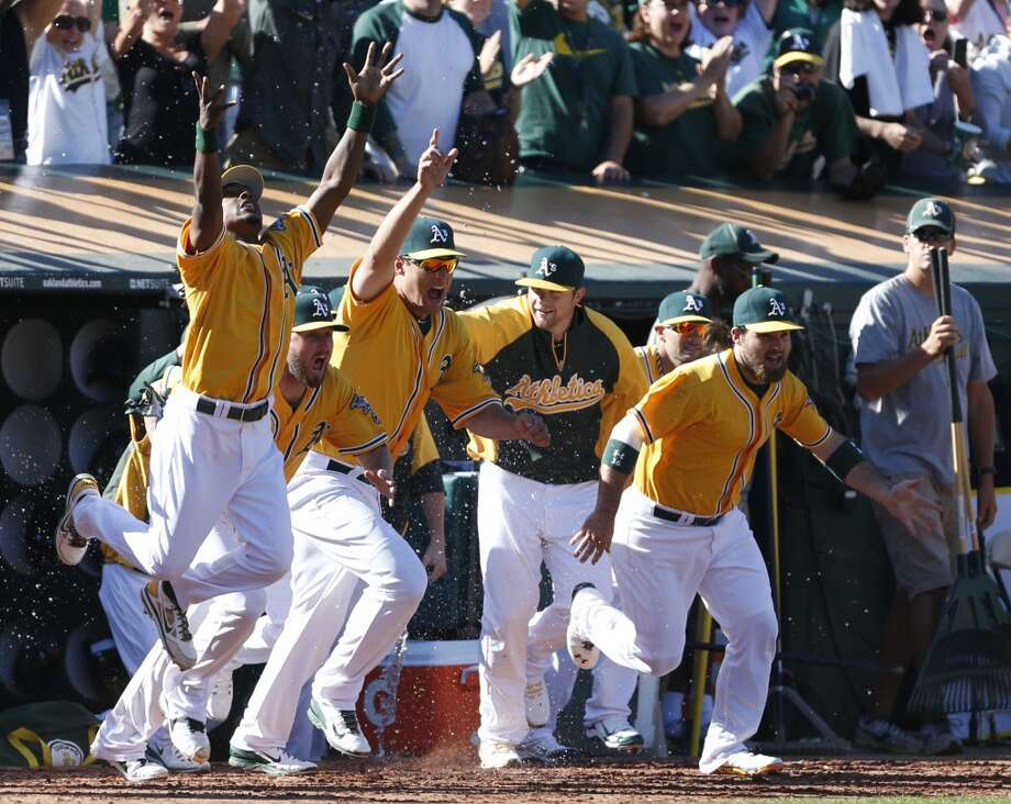 Oakland Athletics' Jemile Weeks, left,  Nate Freiman, center, and Derek Norris, right, celebrate as they run out of the dugout after defeating the Minnesota Twins 11-7. Photo: Beck Diefenbach, Associated Press