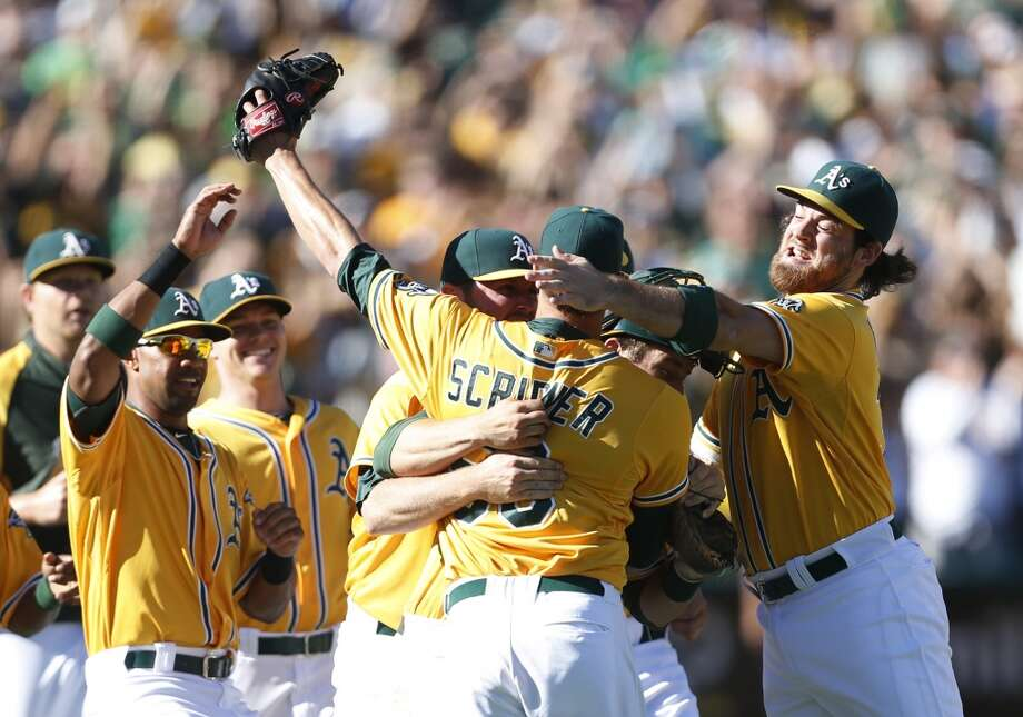 Oakland Athletics' Evan Scribner, center, is congratulated by Chris Young, left, and Derek Norris , right, after defeating the Minnesota Twins 11-7. Photo: Beck Diefenbach, Associated Press