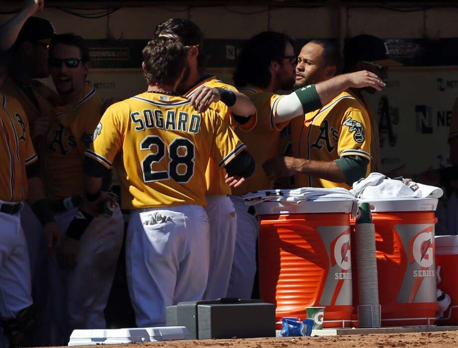Eric Sogard and Coco Crisp, right, celebrate with teammates after learning about the Texas Ranger's loss to the Kansas City Royals, making the Athletics the AL West champions. Photo: Beck Diefenbach, Associated Press