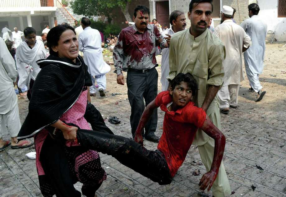 An injured victim of a suicide attack at a church is carried Sunday in Peshawar, Pakistan. The attack killed at least 78, including 34 women and seven children, and injured more than 100. Photo: Mohammad Sajjad / Associated Press