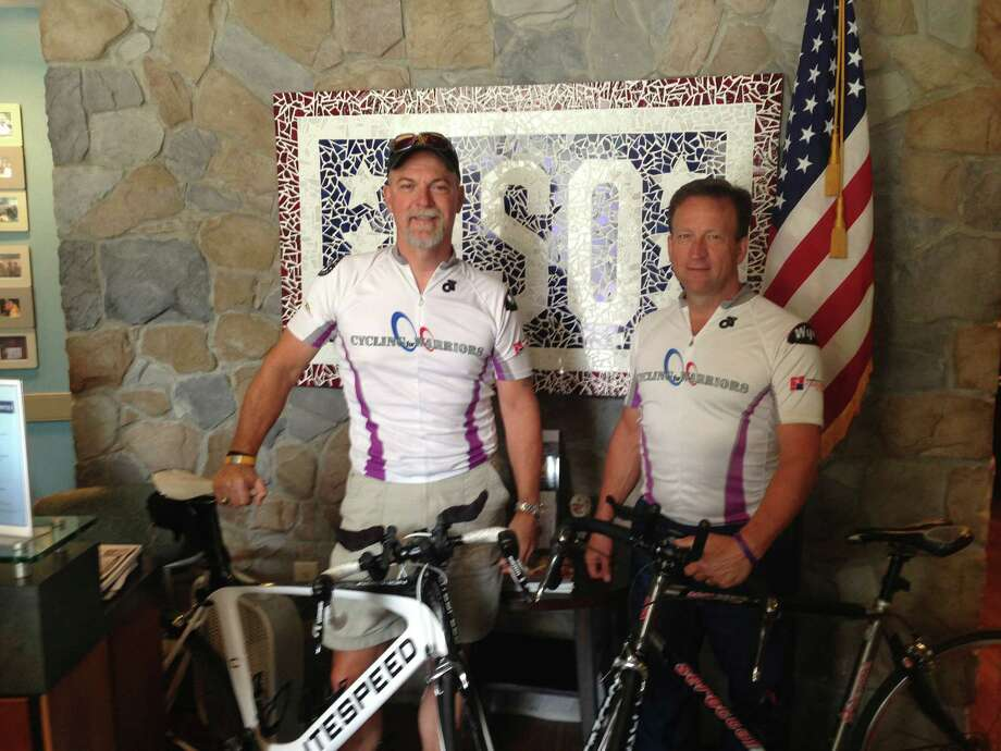 Michael Schwartz, left, and his brother Steve Schwartz paused for a photo at San Antonio's downtown USO location Saturday as their cross-country, fund-raising bicycle ride hit its 21st day. They hope to raise $50,000 on the trip to benefit the Wounded Warrior Project and veterans who need assistance. Photo: Courtesy