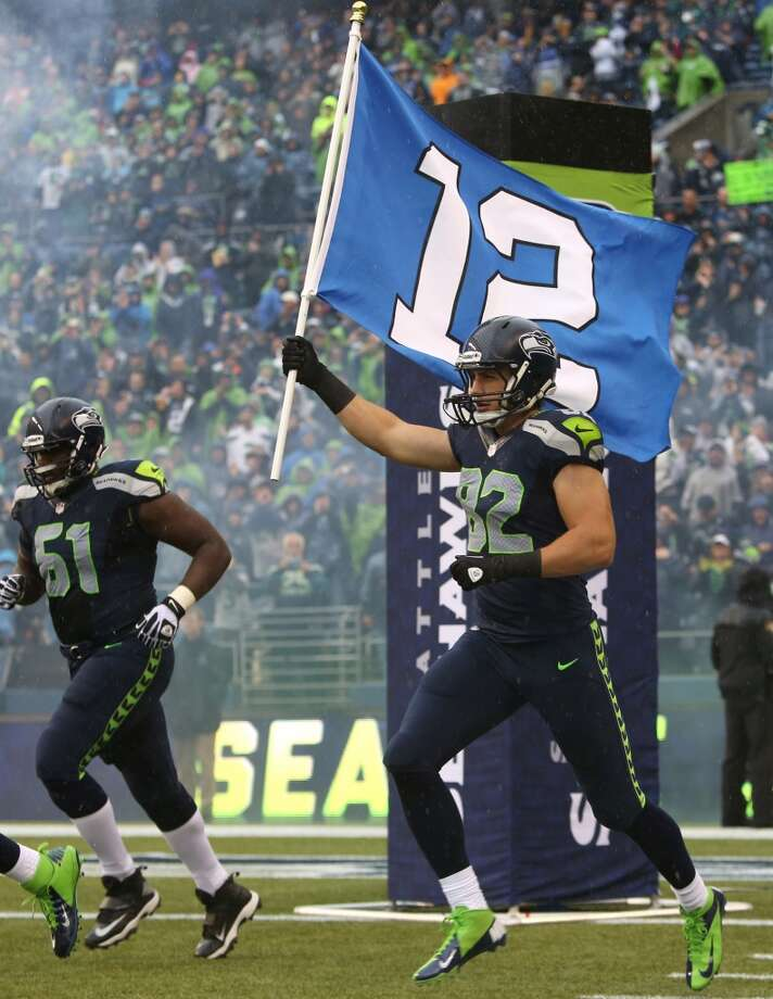Seattle Seahawks player Luke Wilson runs out the 12th Man flag against the Jacksonville Jaguars on Sunday, Sept. 22, 2013 at CenturyLink Field in Seattle. Photo: SEATTLEPI.COM