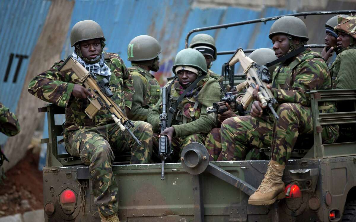 Trucks of soldiers from the Kenya Defense Forces arrive after dawn outside the Westgate Mall in Nairobi, Kenya Sunday, Sept. 22, 2013. Islamic extremist gunmen lobbed grenades and fired assault rifles inside Nairobi's top mall Saturday, killing dozens and wounding over a hundred in the attack. Early Sunday morning, 12 hours after the attack began, gunmen remained holed up inside the mall with an unknown number of hostages. (AP Photo/Ben Curtis) ORG XMIT: ABC102
