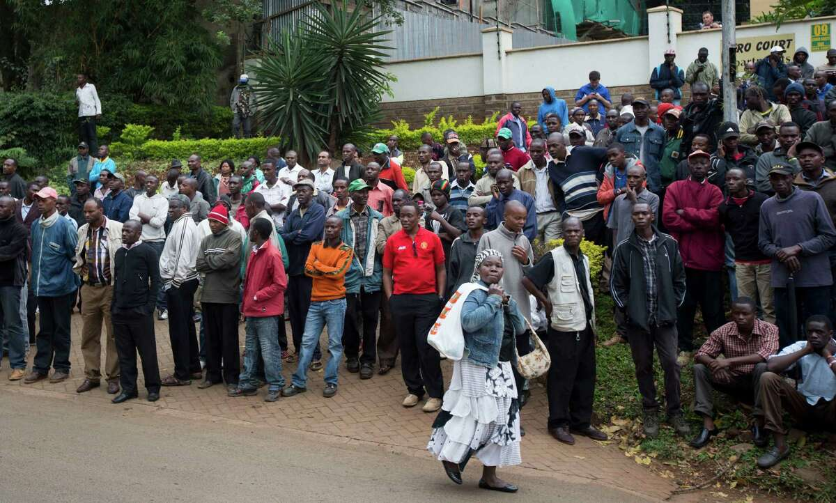 Groups of onlookers gather on a road looking down over the Westgate Mall in Nairobi, Kenya Sunday, Sept. 22, 2013. Multiple barrages of gunfire erupted Sunday morning from the upscale Kenyan mall where there is a hostage standoff with Islamic extremists nearly 24 hours after they attacked using grenades and assault rifles. (AP Photo/Ben Curtis) ORG XMIT: ABC109