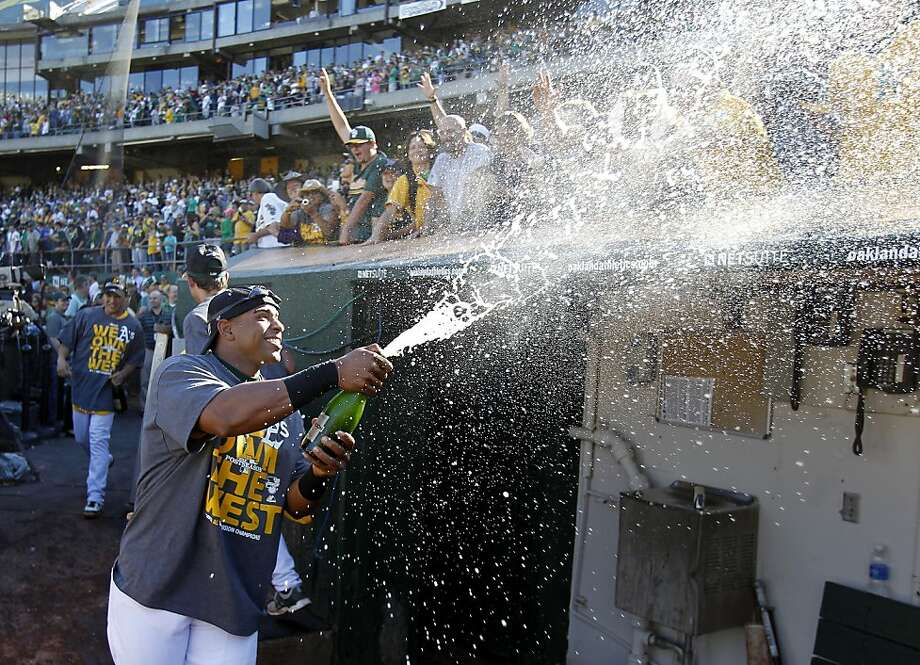 Outfielder Yoenis Céspedes sends a spray of Champagne over the dugout and into celebrating fans after the A's defeated the Minnesota Twins 11-7 and captured the 2013 American League West division championship. Photo: Brant Ward, The Chronicle