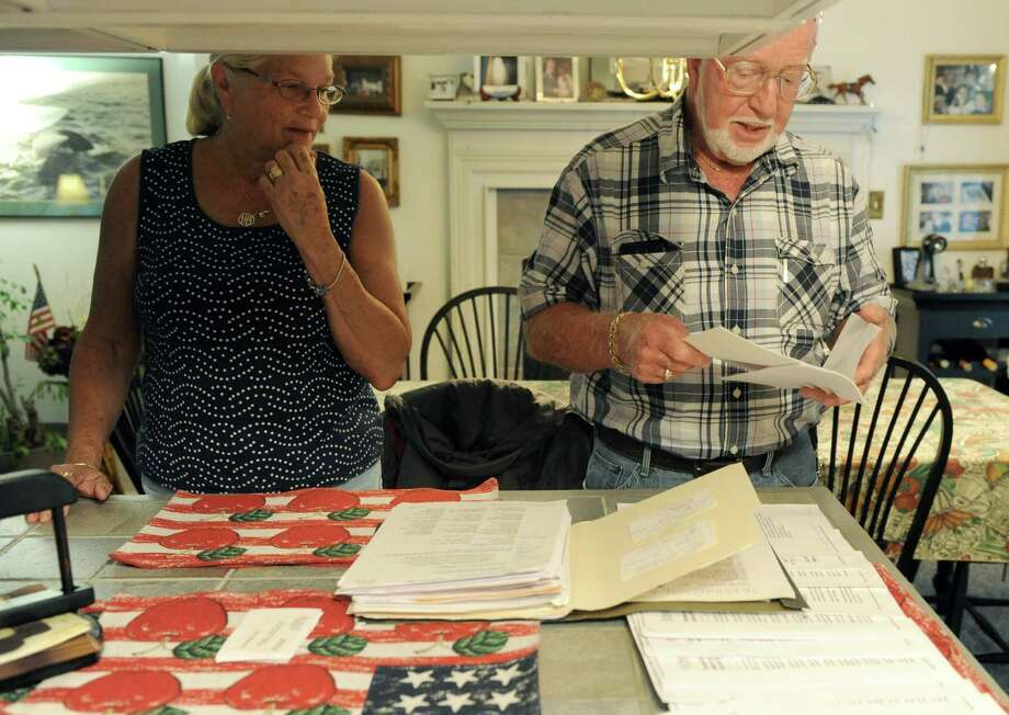 Retirees Daniel & Ileen Duffy look over bills they received for another Daniel J. Duffy Thursday Sept. 12, 2013, in Albany N.Y. The younger Daniel J. Duffy was using the 80-year-old Daniel J. Duffy's address and phone number for years to elude collectors and authorities.  (Michael P. Farrell/Times Union) Photo: Michael P. Farrell / 00023857A