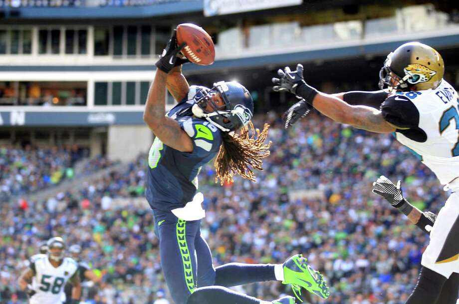 Seattle's Sidney Rice hauls in a 23-yard touchdown pass from Russell Wilson in front of Jacksonville's Josh Evans in the third quarter of the Seahawks' 45-17 win. It was one of two scoring catches for Rice on Sunday. Photo: Stephen Brashear, FRE / FR159797 AP