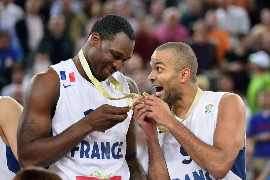 Three-time NBA champion Tony Parker, right, shows Florent Pietrus how excited he is to help France win its first European title. Photo: JURE MAKOVEC, Staff / Jure Makovec/AFP