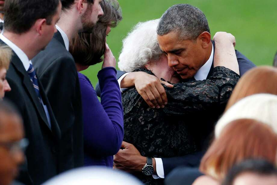 President Barack Obama comforts an unidentifed woman sitting in the family section at a memorial service for the victims of the Washington Navy Yard shooting at Marine Barracks Washington Sunday, Sept. 22, 2013.  A gunman killed 12 people in the Navy Yard on Monday, Sept. 16, 2013, before being fatally shot in a gun battle with law enforcement. The president and first lady Michelle Obama also visited with the victims' families. (AP Photo/Charles Dharapak) Photo: Charles Dharapak, STF / AP