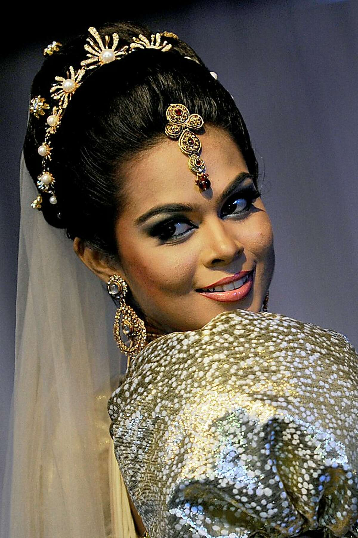 A Sri Lankan model shows off a bridal creation depicting a Sri Lankan bride during a fashion show in Colombo on September 22, 2013. Sri Lanka's economy recorded eight percent plus growth rates for two years running after security forces crushed Tamil Tiger rebels and declared an end to decades of ethnic war in May 2009. AFP PHOTO/ Ishara S. KODIKARAIshara S.KODIKARA/AFP/Getty Images