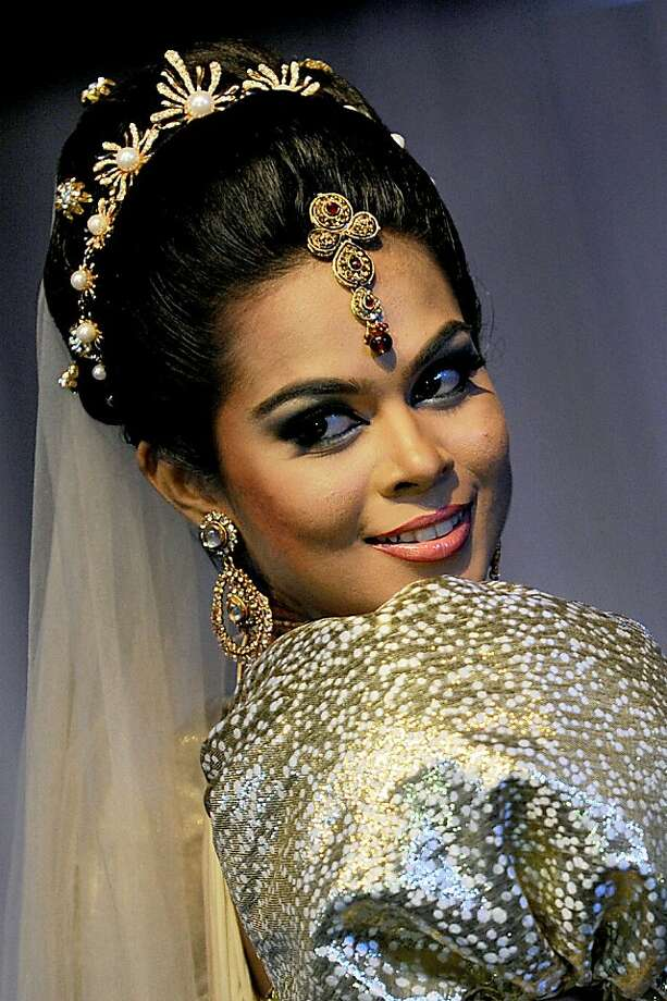 A Sri Lankan model shows off a bridal creation depicting a Sri Lankan bride during a fashion show in Colombo on September 22, 2013. Sri Lanka's economy recorded eight percent plus growth rates for two years running after security forces crushed Tamil Tiger rebels and declared an end to decades of ethnic war in May 2009. AFP PHOTO/ Ishara S. KODIKARAIshara S.KODIKARA/AFP/Getty Images Photo: Ishara S.kodikara, AFP/Getty Images