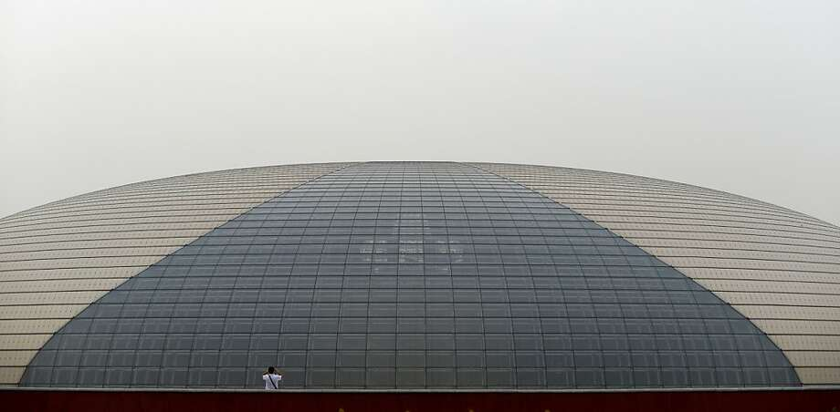 TOPSHOTS A man (L) takes a photo in front of the China National Grand Theater in Beijing on September 22, 2013.  The seven-day holiday built around China's National Day on October 1 sees millions of members of China's newly wealthy and mobile middle-class travel locally and abroad.        AFP PHOTO / WANG ZHAOWANG ZHAO/AFP/Getty Images Photo: Wang Zhao, AFP/Getty Images