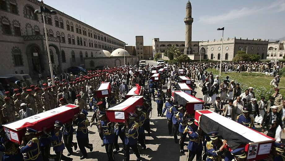 Yemeni honor guards carry the coffins of soldiers who were killed from attacks in Shabwa province by al-Qaida militants, during their funeral in Sanaa, Yemen, Sunday, Sept. 22, 2013. Under a heavy fog, al-Qaida militants disguised in military uniforms launched car bomb attacks on three different security and military posts in southern Yemen on Friday, killing tens of soldiers in the group's biggest attack in the country since last year. (AP Photo/Hani Mohammed) Photo: Hani Mohammed, Associated Press