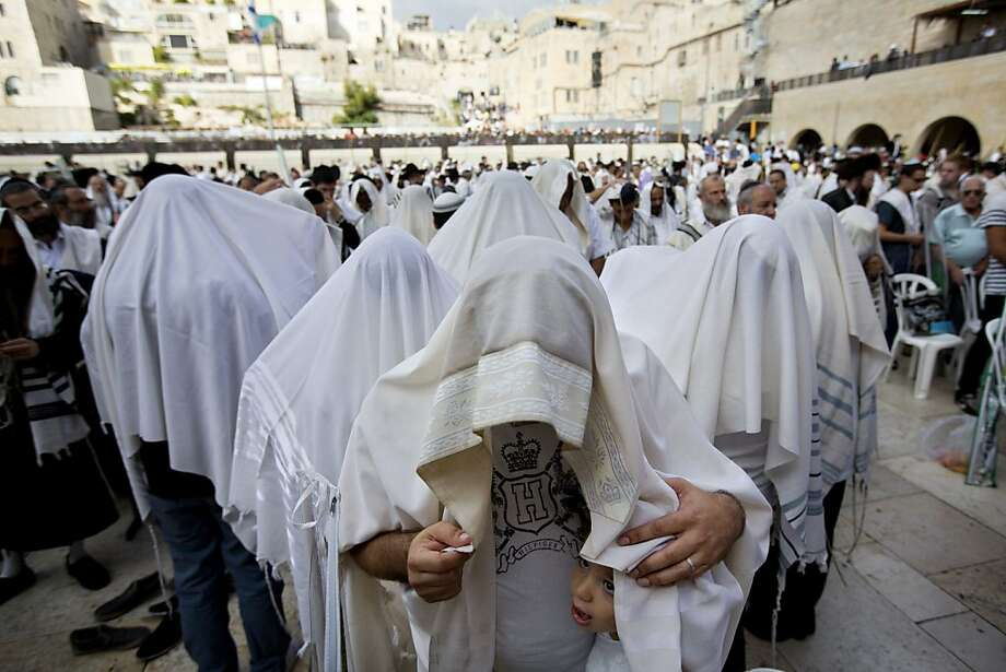 Covered in prayer shawls, Jewish men of the Cohanim Priestly caste participate in a blessing during the holiday of Sukkot, in front of the Western Wall, the holiest site where Jews can pray in Jerusalem's Old City, Sunday, Sept. 22, 2013 . The Cohanim, believed to be descendants of priests who served God in the Jewish Temple before it was destroyed, perform a blessing ceremony of the Jewish people three times a year during the festivals of Passover, Shavuot and Sukkot. (AP Photo/Sebastian Scheiner) Photo: Sebastian Scheiner, Associated Press