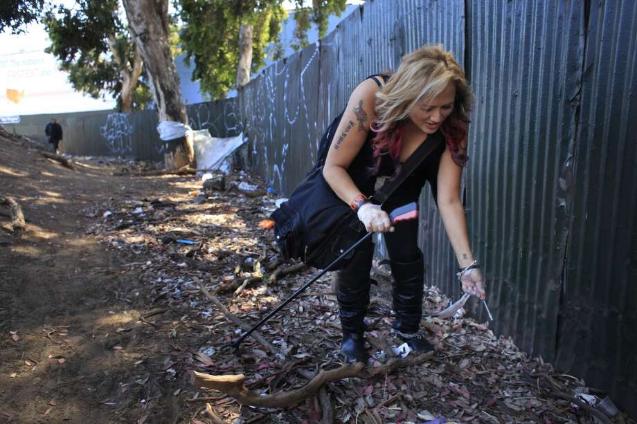 "Picking up used drug needles along the way, Roxanne Cai a.k.a. Rock N Roll, a founding member of ""The Initiative"" move through a homeless encampment during near the Mission district during the group's weekly rounds in San Francisco, Calif. The group is loosely connected to a crime fighting movement known as Real Life Super Heros. Photo: Mike Kepka, The Chronicle"