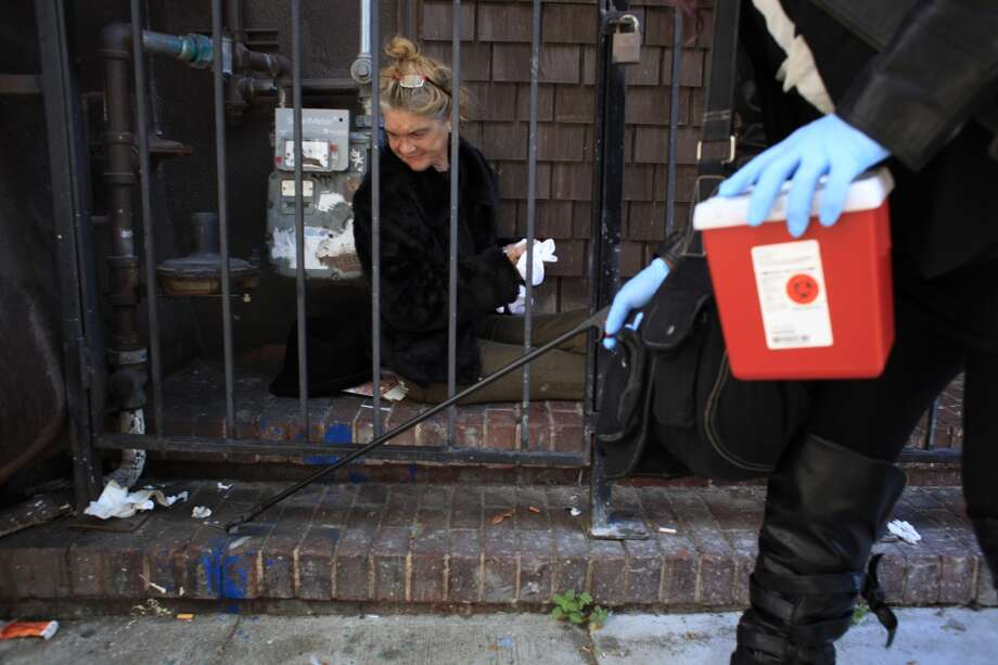 "Roxanne Cai a.k.a. Rock N Roll, a founding member of ""The Initiative"" picks a used needle drug needles lying next a homeless woman named Storm in the Mission district during the group's weekly rounds in San Francisco, Calif. Photo: Mike Kepka, The Chronicle"