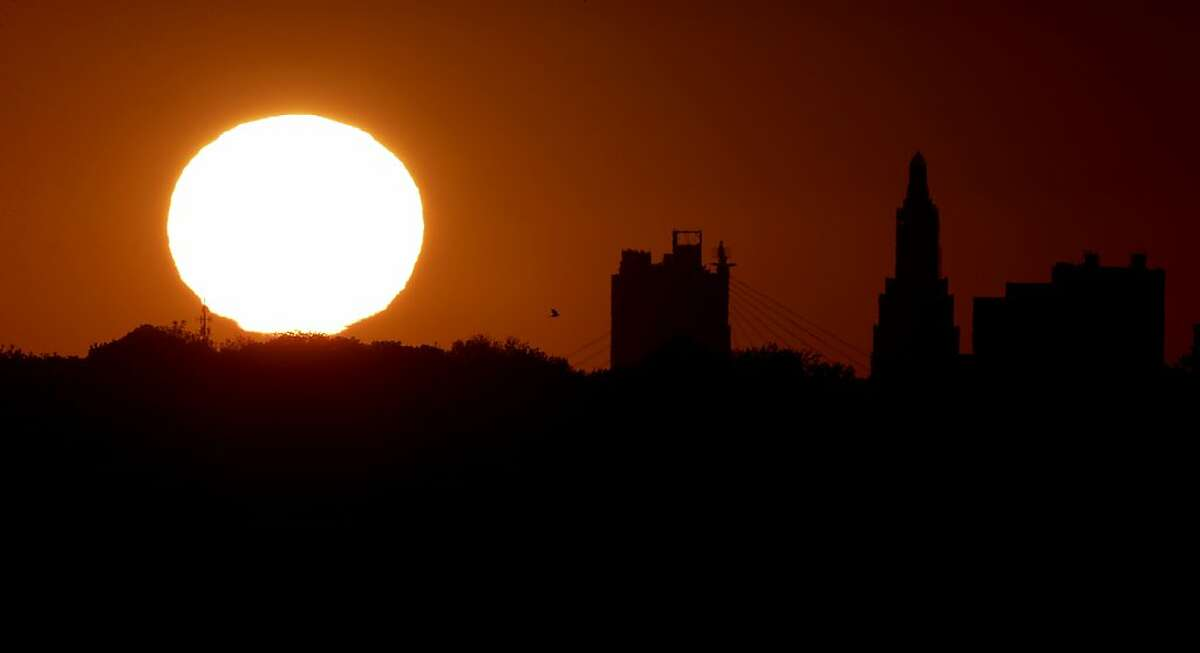 The sun sets beyond the downtown skyline as the autumnal equinox marks the first day of fall Sunday, Sept. 22, 2013, in Kansas City, Mo. (AP Photo/Charlie Riedel)