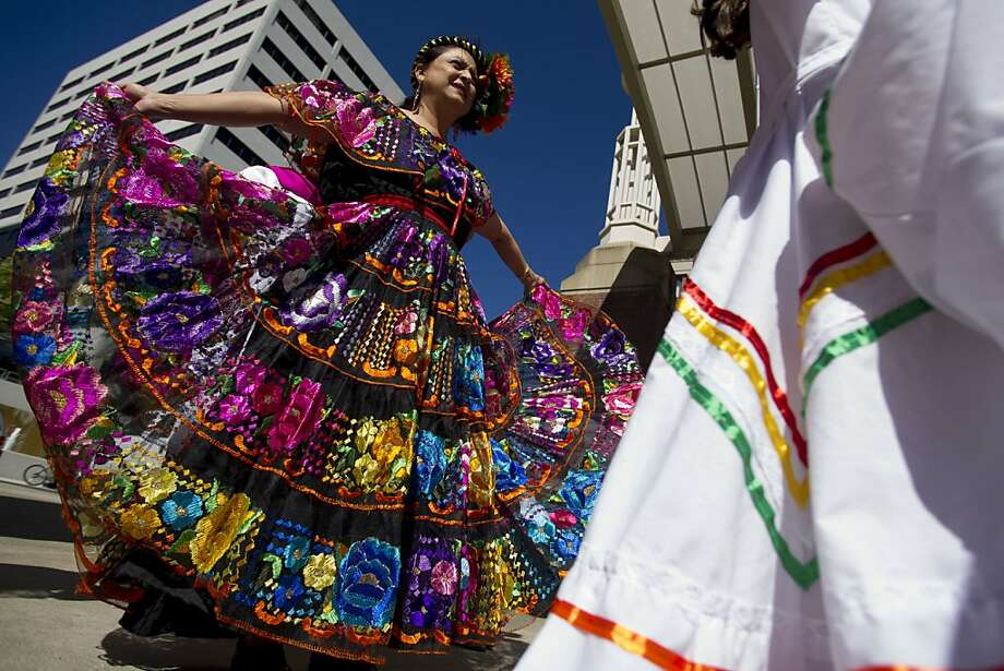 Irma Acevedo flares out her dress just before appearing on stage during the Hola Festival, a festival celebrating Hispanic culture and heritage in Knoxville, Tenn. on  Sunday, Sept. 22, 2013.  (AP Photo/The Knoxville News Sentinel, Saul Young) Photo: Saul Young, Associated Press