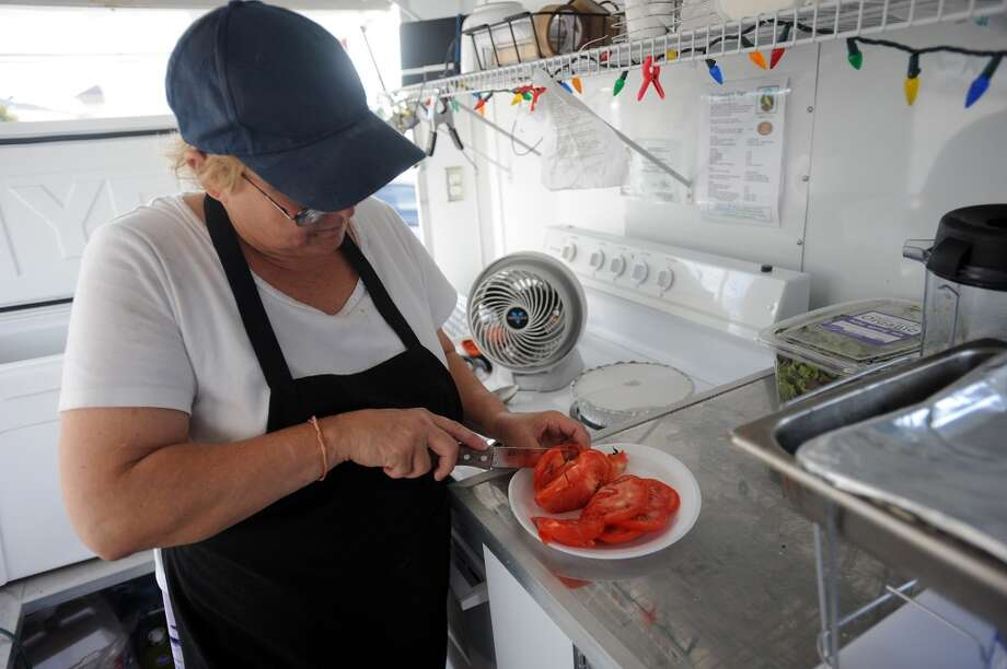 Katie Chenoweth cuts a tomato at the Yellow Bird Farm food truck on Wednesday. The traveling treats and homemade meals can be spotted in front of D'Vine Wine on Calder. Photo taken Wednesday, September 11, 2013 Guiseppe Barranco/The Enterprise Photo: Guiseppe Barranco/The Enterprise